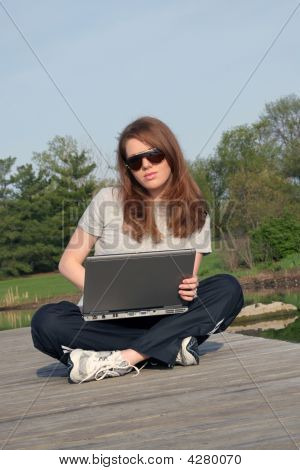 Young Female Working On Computer By The Lake