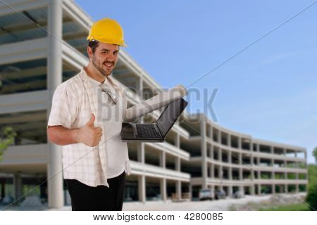 Worker Holding Laptop In Front Of Construction Building
