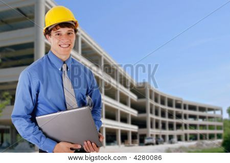 Construction Worker Holding Laptop In Front Of Construction Building