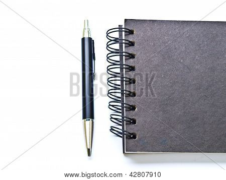 Ballpen And A Black Spiral Binding Notebook Cover On White
