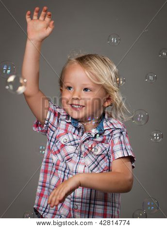 Cute Young Boy Catching Bubbles