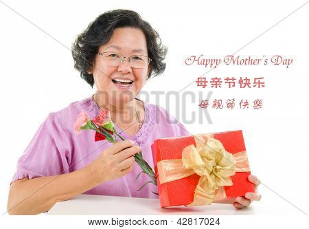 Happy mother's day concept. Asian senior mother showing a gift and carnation isolated on white background.