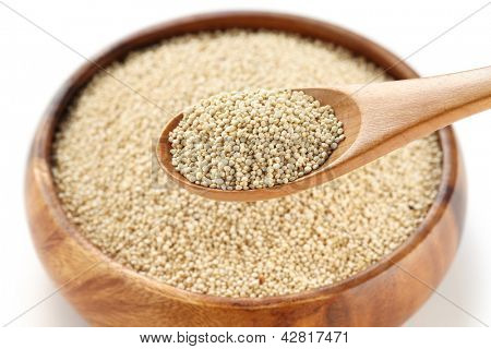 uncooked quinoa in the wooden bowl and spoon