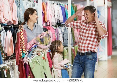 Family shopping. Woman and girl holding clothes with highly surprised father man during shopping at outerwear supermarket