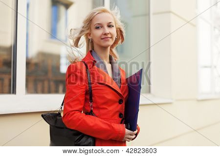 Young businesswoman with a folder against office windows