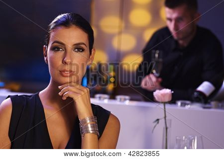 Evening portrait of elegant young woman in restaurant. Man at background.