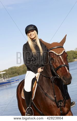 Blonde horsewoman riding horse at riverside looking away.