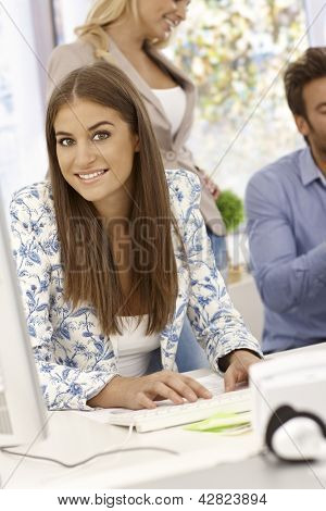 Portrait of attractive young businesswoman sitting at desk, working with computer, smiling, looking at camera.