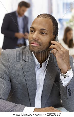 Portrait of handsome young black businessman talking on mobile phone, looking away.