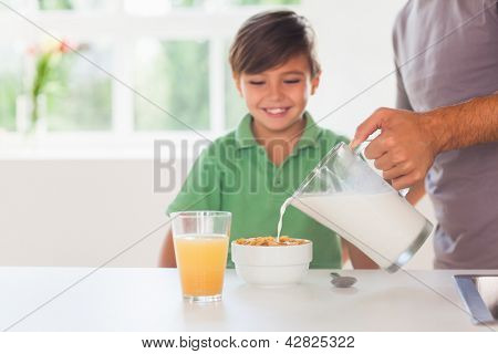 Father putting milk in the cereal of his son in kitchen
