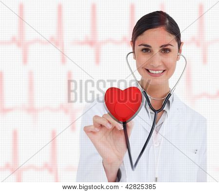 Doctor holding stethoscope up to red heart graphic on ECG background
