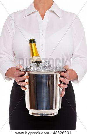 Waitress holding an ice bucket with a bottle of Champagne in it, isolated on a white background.