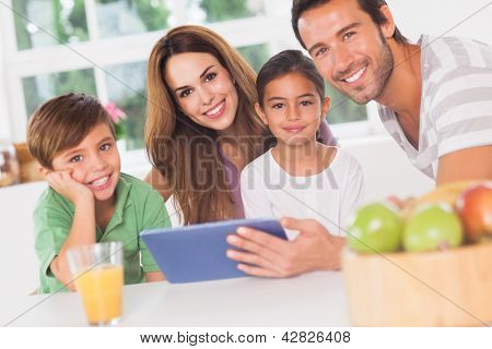 Happy family using a tablet pc in kitchen