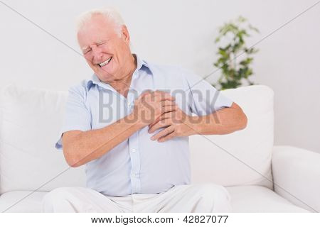 Old man suffering with heart pain on a sofa