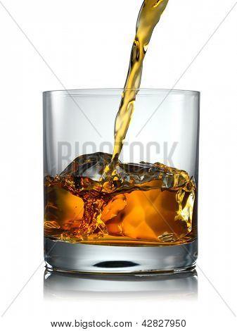 Verter el vaso de whisky escocés y hielo sobre un fondo blanco