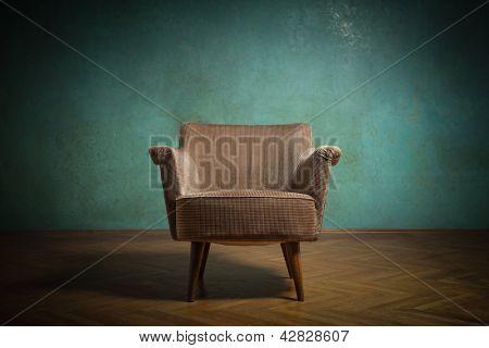 Vieja silla en la sala de grunge con pared verde