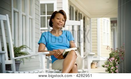 African American Woman Relaxes On Porch Looking Away