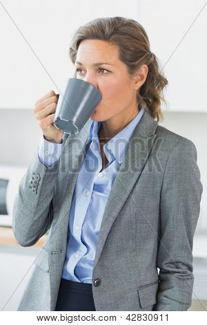 Woman having coffee before work in kitchen