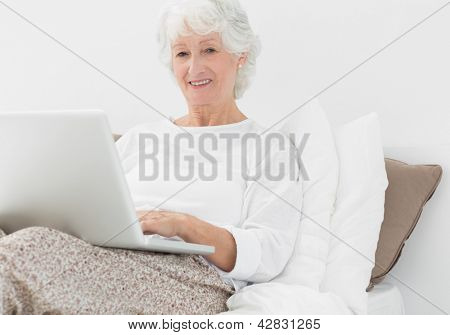Smiling elderly woman typing on her laptop in the bedroom