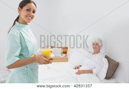 Elderly woman with home nurse in the bedroom