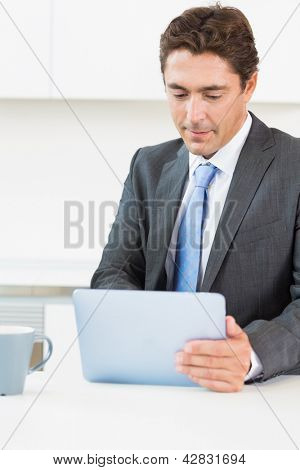 Man using tablet pc before work in kitchen