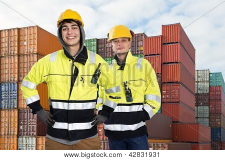 Two happy harbor workers posing in front of a huge stack of containers