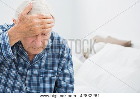 Elderly man suffering on the bed in the bedroom