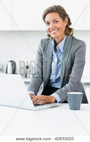 Smiling woman typing on laptop in the kitchen before work