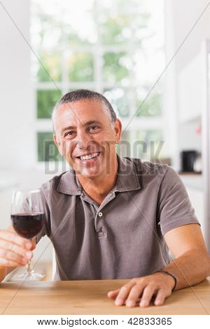 Man holding glass of red wine at the kitchen table