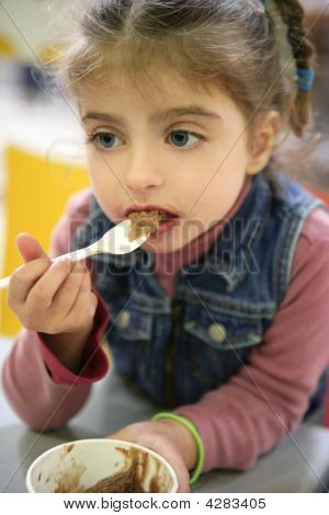 Sweet Girl Gets Dirty Eating Chocolate With Spoon