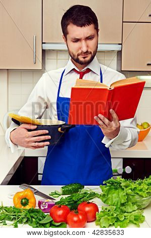 concentrated young man reading cookbook at the kitchen