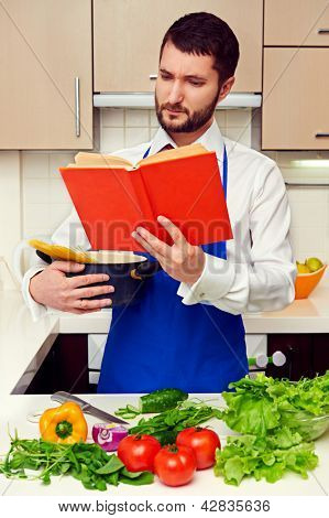 handsome young man reading cookbook attentively at the kitchen