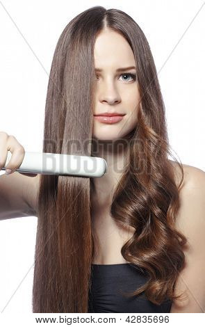 Portrait of young beautiful girl using styler on her shining hair