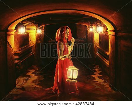 Romantic brunette holding a lantern in a dark dungeon