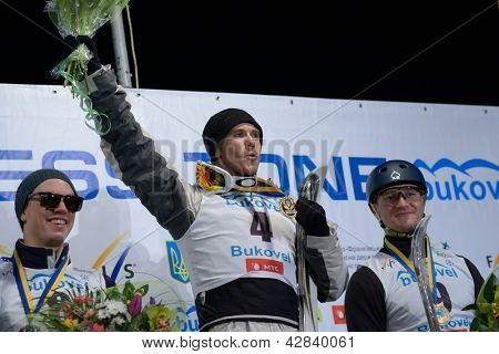 BUKOVEL, UKRAINE - FEBRUARY 23: David Morris, Australia (centre), Dylan Ferguson, USA (left) and Maxim Gustik, Belarus win medals on Freestyle Ski World Cup in Bukovel, Ukraine on February 23, 2013