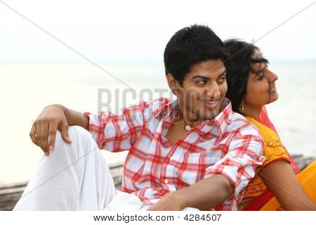 Young Asian Couple Sitting At Sea Shore
