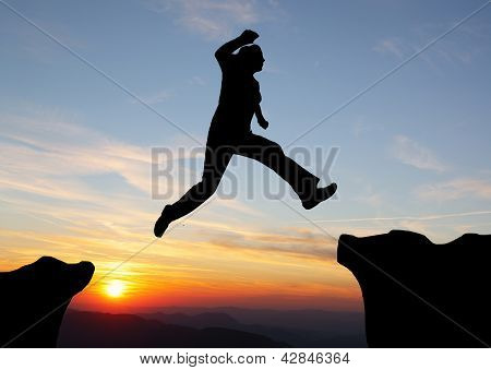 Silhouette Of Hiking Man  Jumping Over The Mountains At Sunset