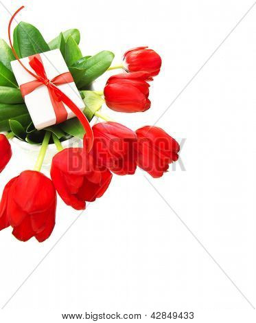 Picture of red tulips flowers and small white gift box on fresh green leaves, romantic still life for happy mothers day isolated on white background, festive border, birthday holiday, cute surprise