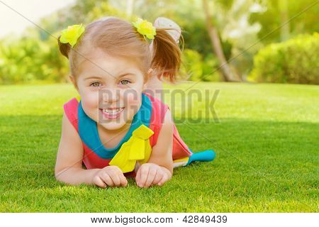 Picture of cute little girl lying down on green grass in park, cheerful child resting on the field on backyard, pretty kid having fun outdoors in springtime, spring nature, sunny day, happy childhood