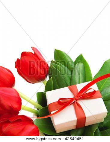 Photo of red tulips flowers and small white gift box on fresh green leaves, romantic still life for happy mothers day isolated on white background, festive present, birthday holiday, cute surprise