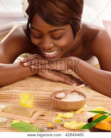 Photo of attractive african woman on massage table in luxury spa salon, smiling female enjoying spa therapy, alternative medicine, white franjipani flower in dark hair, beauty salon, pampering concept