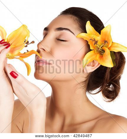 Photo of beautiful arabic female with yellow lily flower in dark hair and in hands enjoying her smell, closeup portrait of cute brunette girl with closed eyes isolated on white background, spa concept