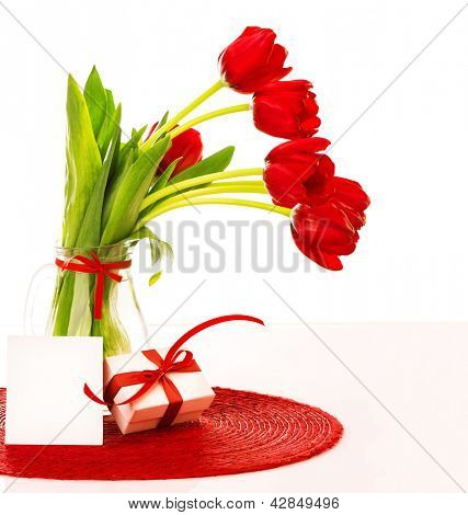 Photo of fresh red tulips bouquet in glass vase with blank card, greeting postcard, romantic bunch of spring flower, springtime holiday, happy mothers day, white gift box with red bow, love concept