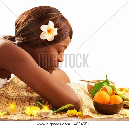 Photo of lovely African woman with closed eyes and white franjipani flower in head relaxed on massage table in luxury spa salon, enjoying dayspa, healthy lifestyle, beauty treatment, pampering concept