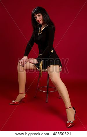 Young Brunette Woman Sitting On A Chair On A Red Background