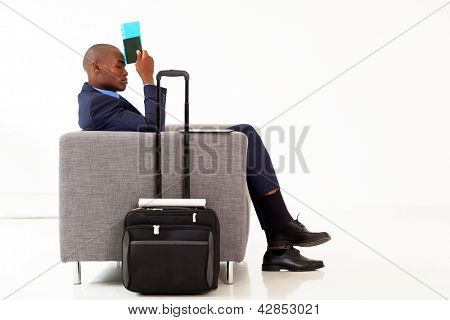 tired african american businessman resting in airport VIP lounge