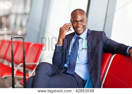 african business traveler talking on cell phone at airport