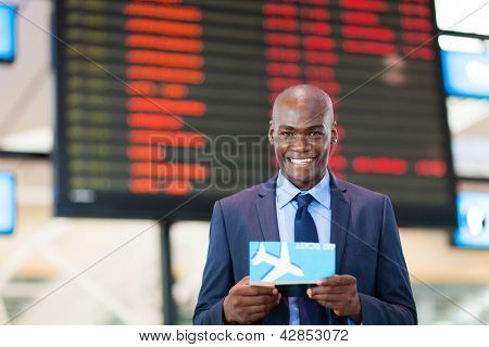 African business traveler in front of flight information board in airport