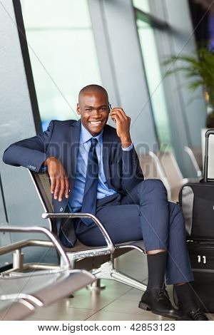 african business traveller talking on mobile phone in airport
