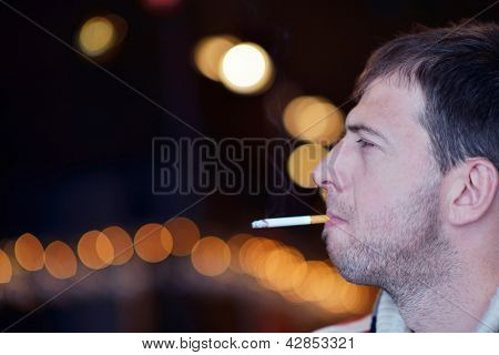 The man smokes a cigaret against a dark background